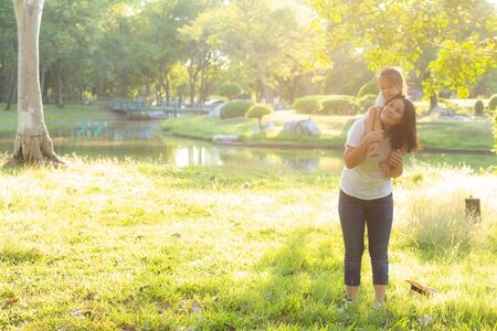 Beautiful young asian mother carrying little daughter with smile, child ride the neck on mom with happiness and cheerful together in the park, lifestyle family with enjoy and fun concept.