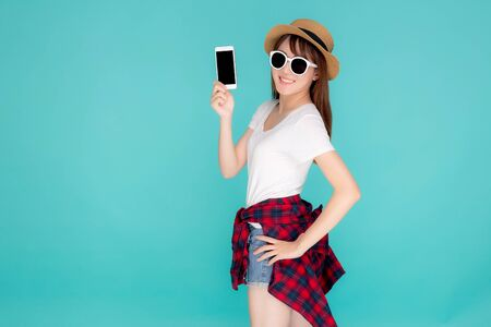 Beautiful young asian woman showing smart mobile phone for presenting something in travel summer trip in vacation isolated on blue background, asia girl holding smartphone, holiday concept.