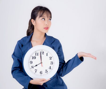 Beautiful portrait young business asian woman smiling holding clock isolated on white background, happy businesswoman schedule time of work, confident girl showing watch, management time concept.