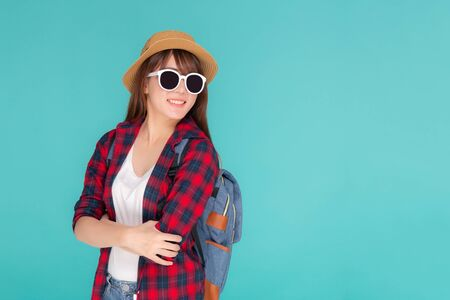 Beautiful portrait young asian woman wear sunglasses and hat smile excited and confident enjoy summer holiday isolated blue background, model girl cheerful having backpack in vacation, travel concept. Stock Photo