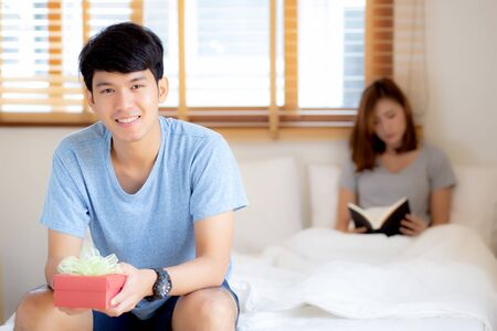 Beautiful young asian couple in love surprise gift box in bedroom at home, family anniversary with enjoy and romantic together wife and husband with relationship, Celebrating Valentine Day concept.