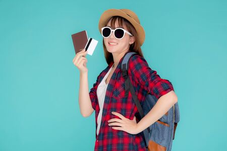 Beautiful young asian woman wear hat and sunglasses with showing credit card and passport to travel summer trip isolated on blue background, girl journey in vacation with payment finance on card.
