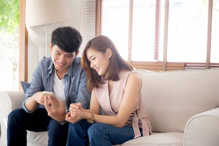 Young asian couple or friend looking smart mobile phone with enjoy at living room, happy family relax and fun media entertainment on smartphone on sofa together at home, lifestyle concept.