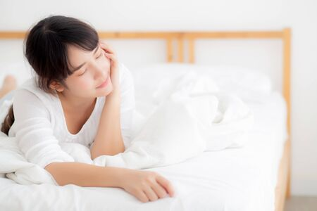 Beautiful portrait young asian woman lying and smile while wake up with sunrise at morning, girl with happy annd fun in the bedroom, lifestyle and relax concept.