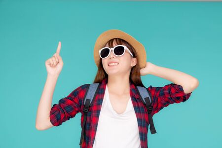 Beautiful portrait young asian woman wear sunglasses and hat smile excited and pointing something travel summer trip in holiday isolated blue background, girl cheerful having backpack in vacation.