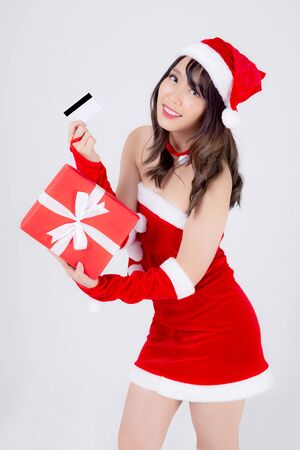 Beautiful portrait young asian woman happy holding credit card and red gift box in Christmas holiday isolated on white background, beauty asia girl surprise shopping with credit card in xmas day.