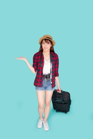Beautiful young asian woman smiling and travel summer trip with luggage and presenting show something for abroad in vacation, asia girl having camera walking and pull suitcase for journey in holiday. Archivio Fotografico - 133661794