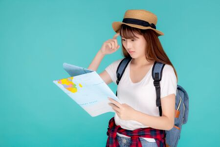 Beautiful portrait young asian woman travel holding and looking a paper map isolated on blue background, asia girl think and idea search journey with direction in vacation trip for leisure. Archivio Fotografico - 133661795