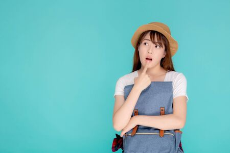 Beautiful portrait young asian woman wearing hat smiling and thinking idea with holding backpack to travel summer trip in holiday in vacation isolated blue background, tourist asia girl is having bag. Archivio Fotografico - 133661796