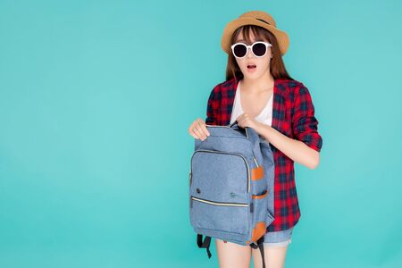 Beautiful portrait young asian woman wear sunglasses and hat open backpack and surprise travel summer trip holiday in vacation isolated on blue background, tourist girl excited and shocked having bag. Archivio Fotografico - 133666636