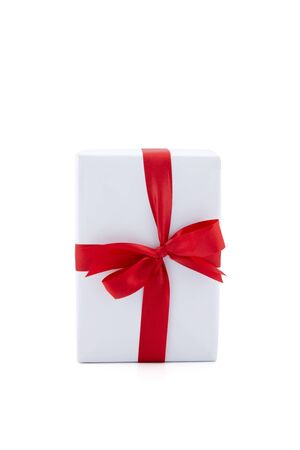 White gift box and red ribbon in season Christmas and new year isolated on white background, luxury present for birthday or anniversary with surprise in package for happy, holiday concept. Stock Photo