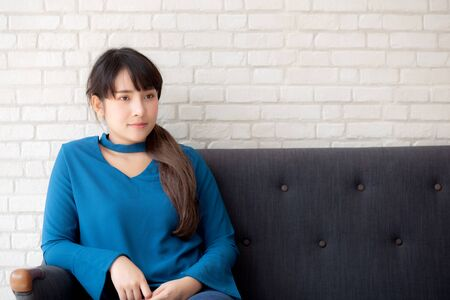 Beautiful portrait young asian woman sitting and smiling happy and looking at camera on sofa with casual at living room, girl cheerful and relax on couch at home, lifestyle concept. Archivio Fotografico - 133670313