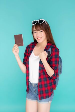 Beautiful portrait young asian woman wear sunglasses on head smile excited and enjoy summer holiday isolated blue background, asia girl hipster cheerful holding passport for travel trip concept. Archivio Fotografico - 133670319