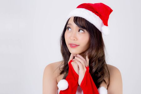 Beautiful portrait young asian woman Santa costume wear hat smiling and thinking in holiday xmas, beauty model asia girl cheerful and happiness celebrating in Christmas isolated on white background. Archivio Fotografico - 133670322