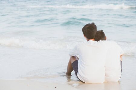Back view homosexual portrait young asian couple sitting hug together on beach in summer, asia gay going tourism for leisure and relax with romantic and happy in vacation at sea, LGBT legal concept. Archivio Fotografico - 133663745