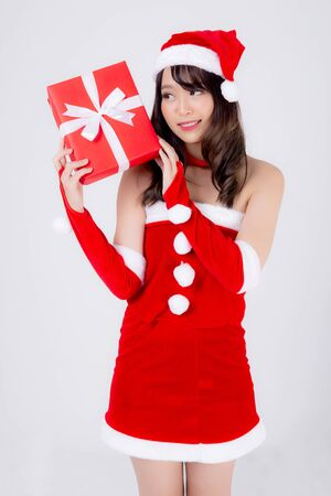 Beautiful portrait young asian woman happy holding red gift box with excited in xmas holiday isolated on white background, asia girl surprise and celebrating in festive Christmas and new year. Archivio Fotografico - 133663746