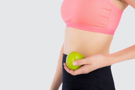 Closeup beautiful young asian woman in sport clothing satisfied and holding green apple isolated on white background, girl asia have shape and wellness, exercise for fit with health concept. Archivio Fotografico - 133663768