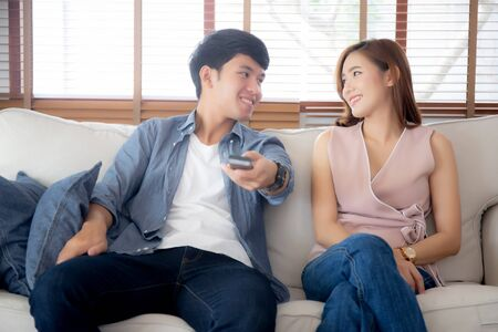 Beautiful young asian couple holding remote and watching tv or video streaming on sofa with relax and happy in living room at home, lifestyle family leisure with entertainment enjoy together on couch. Archivio Fotografico - 133663748