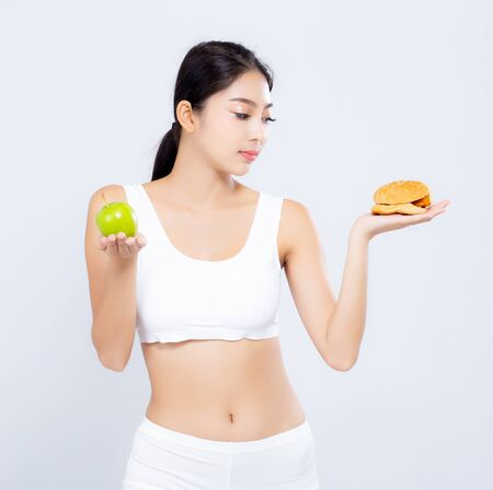 Beautiful young asian woman slim shape with diet choosing fresh salad vegetable and hamburger isolated on white background, food healthy with control for weight loss with calories, nutrition and lifestyle concept.