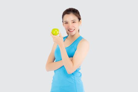 Beautiful portrait young asian woman in sport clothing with satisfied and holding green apple isolated on white background, girl asia have shape and wellness, exercise for fit with health concept. Archivio Fotografico - 133663753