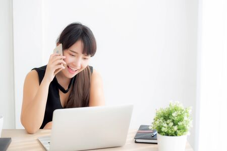 Beautiful young freelance asian woman smiling working on laptop computer and talking mobile smart phone at desk office with professional, girl using notebook, business and lifestyle concept. Archivio Fotografico - 133663754