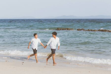 Homosexual portrait young asian couple running with cheerful together on beach in summer, asia gay going tourism for leisure and relax with happiness in vacation at sea, LGBT legal concept. Archivio Fotografico - 133663784