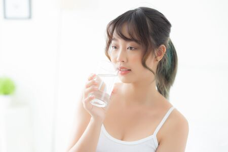 Beautiful portrait young asian woman caucasian smiling with nutrition thirsty and drinking glass of water mineral with fresh and happy, asia girl diet for healthy care and wellness, lifestyle concept. Archivio Fotografico - 133663787