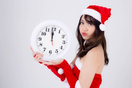 Beautiful portrait young asian woman in Santa dress holding clock with excited in xmas holiday isolated on white background, beauty asia girl celebrating success in festive Christmas day or new year. Archivio Fotografico - 133663793