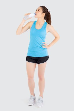 Beautiful young asian woman fit shape drinking water after workout and exercise isolated on white background, girl thirsty after aerobic tired for refresh, model fitness healthy and wellness concept. Archivio Fotografico - 133663794
