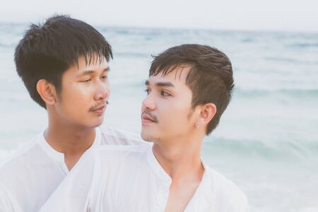 Homosexual portrait young asian couple standing hug and look together on beach in summer, asia gay going tourism for leisure and relax with romantic and happy in vacation at sea, LGBT legal concept. Archivio Fotografico - 133664228