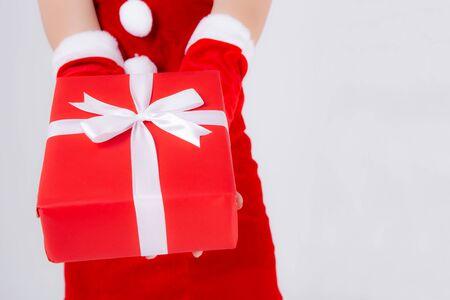 Primo piano mano donna che tiene la scatola presente nel giorno di Natale con sorpresa isolata su sfondo bianco, braccio ragazza felice dare scatola regalo rossa con carta da imballaggio e nastro bianco in vacanza di Natale o compleanno. Archivio Fotografico