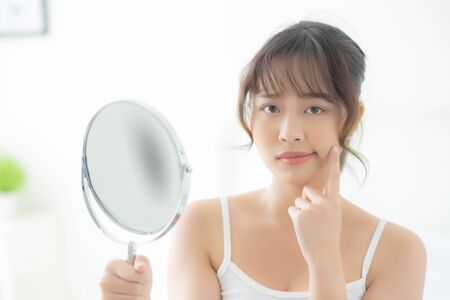 Beautiful young asian woman looking the mirror with acne problem at bedroom, trouble of beauty on face, zit treatment, asia girl is pimple having worry and displeased, skincare and healthy concept. Archivio Fotografico - 133666359