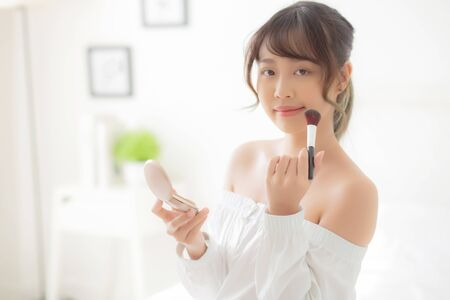 Beauty portrait young asian woman smiling with face looking mirror applying makeup with brush cheek in the bedroom, beautiful girl holding blusher facial, skin care and cosmetic concept. Archivio Fotografico - 133666367