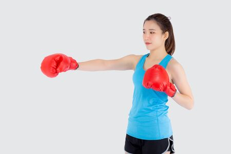 Beautiful portrait young asian woman wearing red boxing gloves with strength isolated on white background, girl workout exercise is sport training with punch, health concept. 版權商用圖片