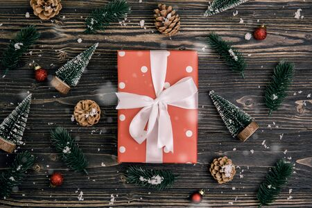 Christmas holiday composition with red gift box and tag decoration on wooden background, new year and xmas or anniversary with presents on wood table in season, top view or flat lay. Archivio Fotografico - 133679307