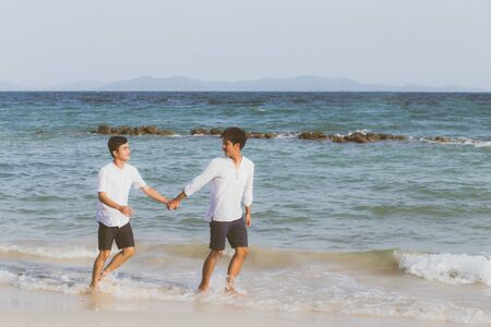 Homosexual portrait young asian couple running with cheerful together on beach in summer, asia gay going tourism for leisure and relax with happiness in vacation at sea, LGBT legal concept. Archivio Fotografico - 133666373