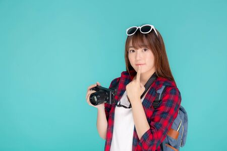 Beautiful young asian woman thinking idea travel trip summer isolated on blue background, asia girl having activity hobby take a photo holding camera, tourist journey in vacation and holiday. Archivio Fotografico - 133670329