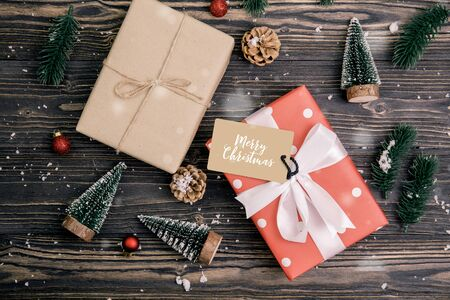 Christmas holiday composition with red gift box and tag decoration on wooden background, new year and xmas or anniversary with presents on wood table in season, top view or flat lay. Standard-Bild - 134079049