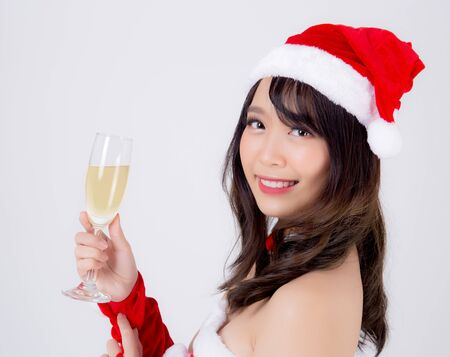Beautiful portrait young asian woman in Santa holding glass of champagne with party celebrating in xmas holiday isolated on white background, asia girl drink beverage, Christmas and new year concept. Standard-Bild - 134078901