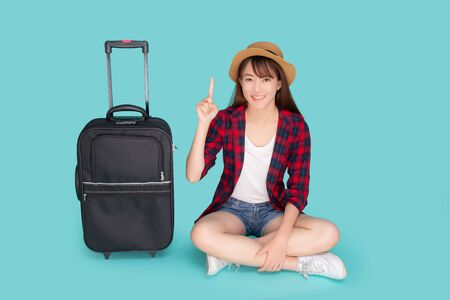 Beautiful portrait young asian woman presenting and pointing something and luggage for travel in summer vacation isolated on blue background, asia girl sitting and suitcase for journey concept. Standard-Bild - 134078902