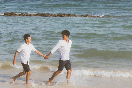 Homosexual portrait young asian couple running with cheerful together on beach in summer, asia gay going tourism for leisure and relax with happiness in vacation at sea, LGBT legal concept.