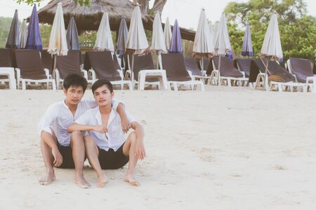 Homosexual portrait young asian couple sitting hug together on beach in summer, asia gay going tourism for leisure and relax with romantic and happiness in vacation at sea, LGBT legal concept.