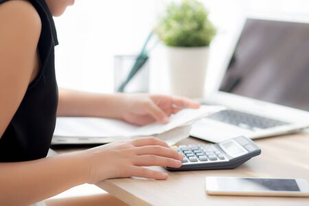 closeup hand woman calculating expenses household and writing notebook on desk, girl checking bill and stress and note, female worry debt and tax, finance and business concept. Banque d'images