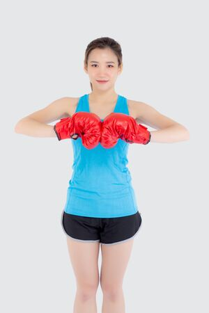 Beautiful portrait young asian woman wearing red boxing gloves with strength and strength isolated on white background, girl workout exercise is sport training with punch, health concept.