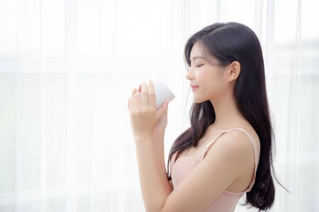 Beautiful young asian sexy woman in underwear drinking coffee near windows in the morning, girl with seductive figure fit drinking beverage for relax and resting after wake up, lifestyle concept.