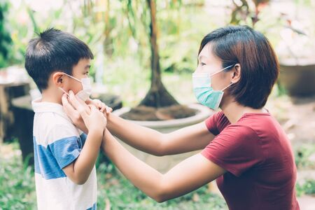 Mother take care son with face mask for protection disease flu or covid-19 outdoors, mom wearing on medical mask with child safety for protect outbreak of pandemic in public, medical concept. Stock Photo