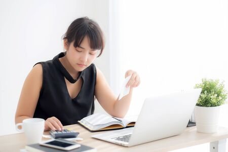 Beautiful young asian woman calculating expenses household and writing notebook on desk, girl checking bill and stress and note, female worry debt and tax, finance and business concept.