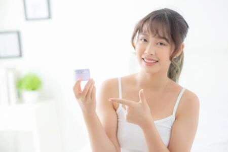 Beautiful portrait young asian woman holding and pointing presenting cream or lotion product, beauty asia girl show cosmetic makeup and moisturizing for skin care, healthy and wellness concept. Banque d'images