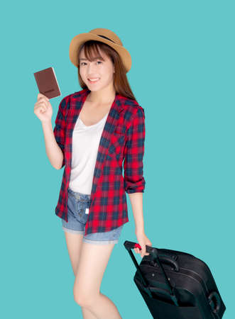 Beautiful young asian woman smiling and travel summer trip with luggage and holding passport for abroad in vacation, happy asia girl cheerful walking and pull suitcase for journey in holiday.