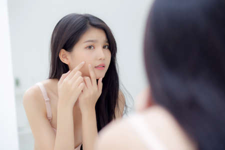 Beautiful young asian woman looking the mirror and touch face is a acne, zit treatment, beauty girl problem beauty and skin with wrinkled on facial in the room at home, makeup and cosmetic concept.